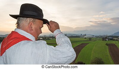 Man wearing traditional clothing looking at fields - Farmer...