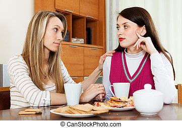 brunette woman has problem, girlfriend consoling her at...