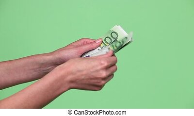 Woman hands counting euro cash money over green background
