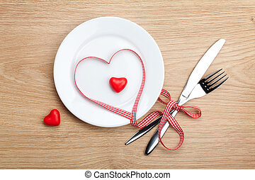 Valentines Day heart shaped red ribbon over plate with...