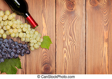 Red wine bottle and bunch of grapes on wooden table...