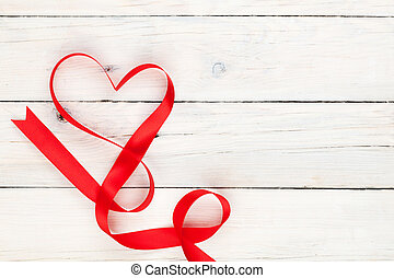Valentines day heart shaped ribbon over white wooden table...