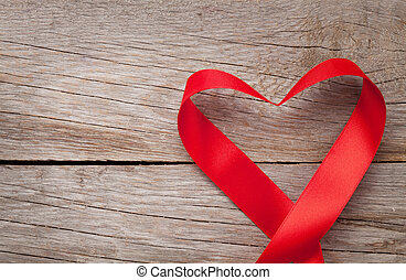 Valentines day heart shaped ribbon over wooden table...