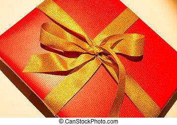 red christmas present with golden loop