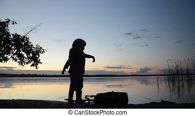 Little girl playing on the shore of the lake in the evening