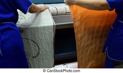 Workers loads clean towels in ironing machine - View of...