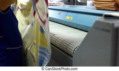 Worker loads bedsheet in ironing machine - View of worker...