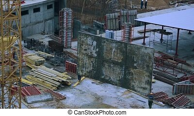 Workers remove a concrete slab with a crane