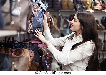 girl chooses bag at shop