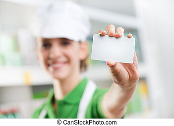 Sales clerk holding a blank business card - Female sales...