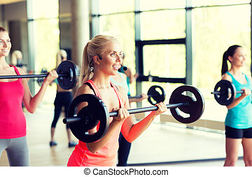 group of women with barbells in gym - fitness, sport,...