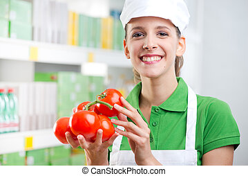 Sales clerk with fresh tomatoes - Young female sales clerk...