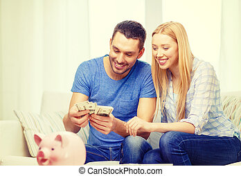 smiling couple counting money at home - love, family,...