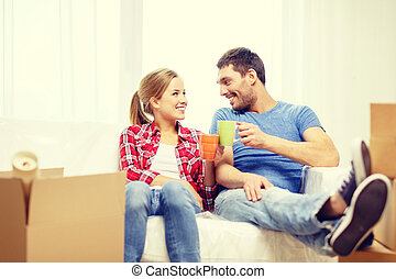 smiling couple relaxing on sofa in new home - moving, home...