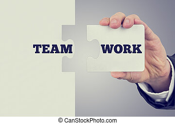 Two matching puzzle pieces with the word Teamwork spread...