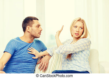 unhappy couple having argument at home - love, family and...