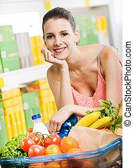Shopping at supermarket - Young smiling woman shopping at...