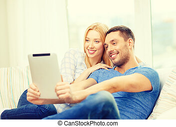 smiling happy couple with tablet pc at home - love, family,...