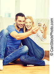 smiling couple taking picture with digital camera - love,...