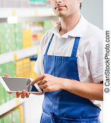 Sales clerk with tablet - Young sales clerk holding a...