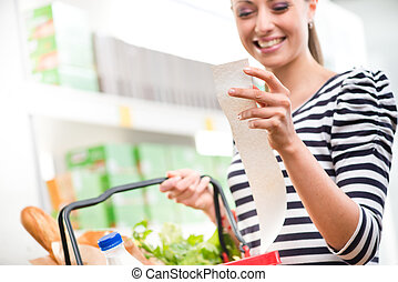 Cheap grocery store prices - Smiling young woman holding a...