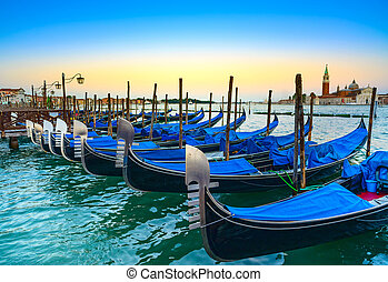Venice, gondolas or gondole on sunset and church on background.