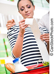 Couple checking a long supermarket receipt - Young couple at...
