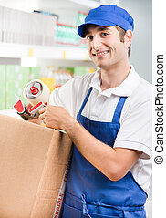 Sales clerk with cardboard box - Young attractive sales...