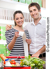 Cheap grocery store prices - Smiling couple at store holding...