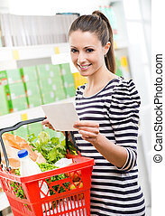 Woman with shopping list - Woman at supermarket holding a...