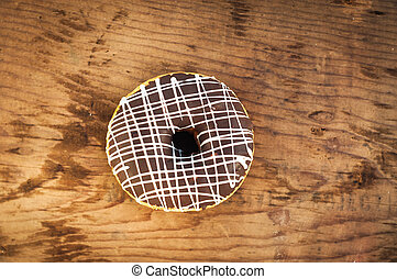 Bright donut on wooden background.