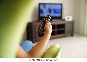 Woman on sofa watching tv changing channel with remote -...