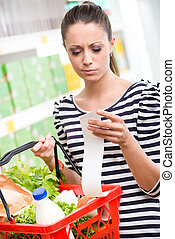 Shocking prices at supermarket - Astonished young woman with...