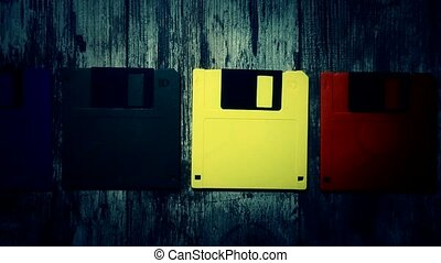 Floppy disks of different colors on a vintage wooden...