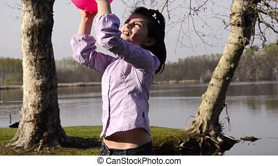 kid is playing with a fuchsia ball