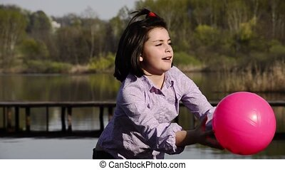kid is playing with a fuchsia ball - young girl playing ball...