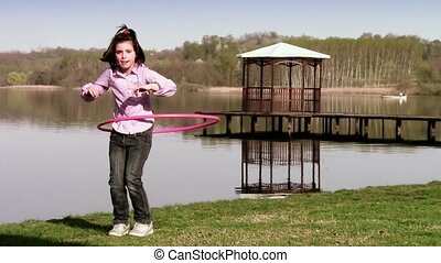 hula hoop - little girl hula hooping near a lake