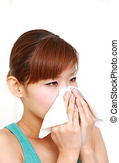 woman sneezing - young Japanese woman sneezing with allergy...
