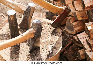 woodsplitting log - A large block of wood holds several axes...