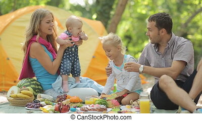 Cheerful family having picnic with fruits