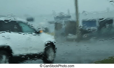 View through rainy windshield. White SUV turns and traffic...