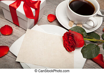 postcard blank, cup of coffee and red rose on table