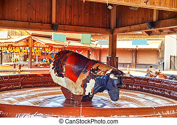 Ride the bull in park amusement. - Ride of the bull in park...