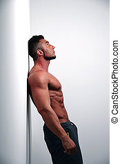 Portrait of muscular man leaning against the wall and...