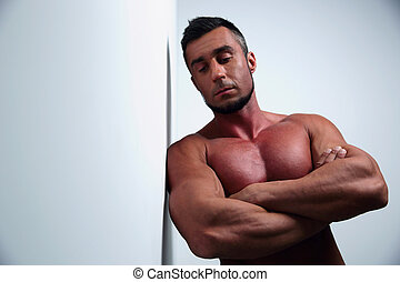 Portrait of a pensive muscular man with arms folded leaning...
