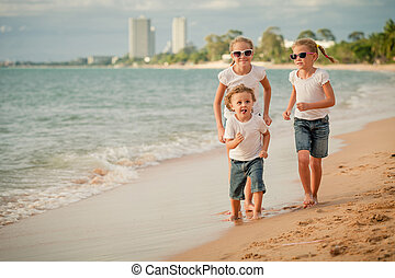 Three happy children running on the beach at the day time