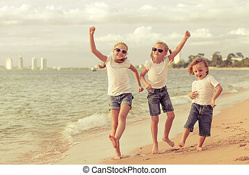 Three happy children dancing on the beach at the day time