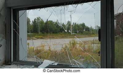 View through broken window Traffic passing on the road Two...