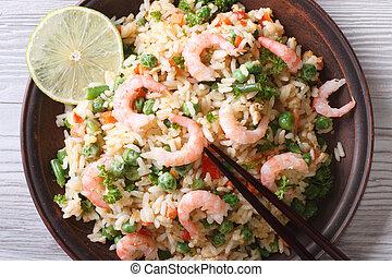 Asian fried rice with seafood closeup, horizontal top view -...