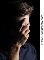 Worried or embarrassed man on black - Worried or embarrassed...